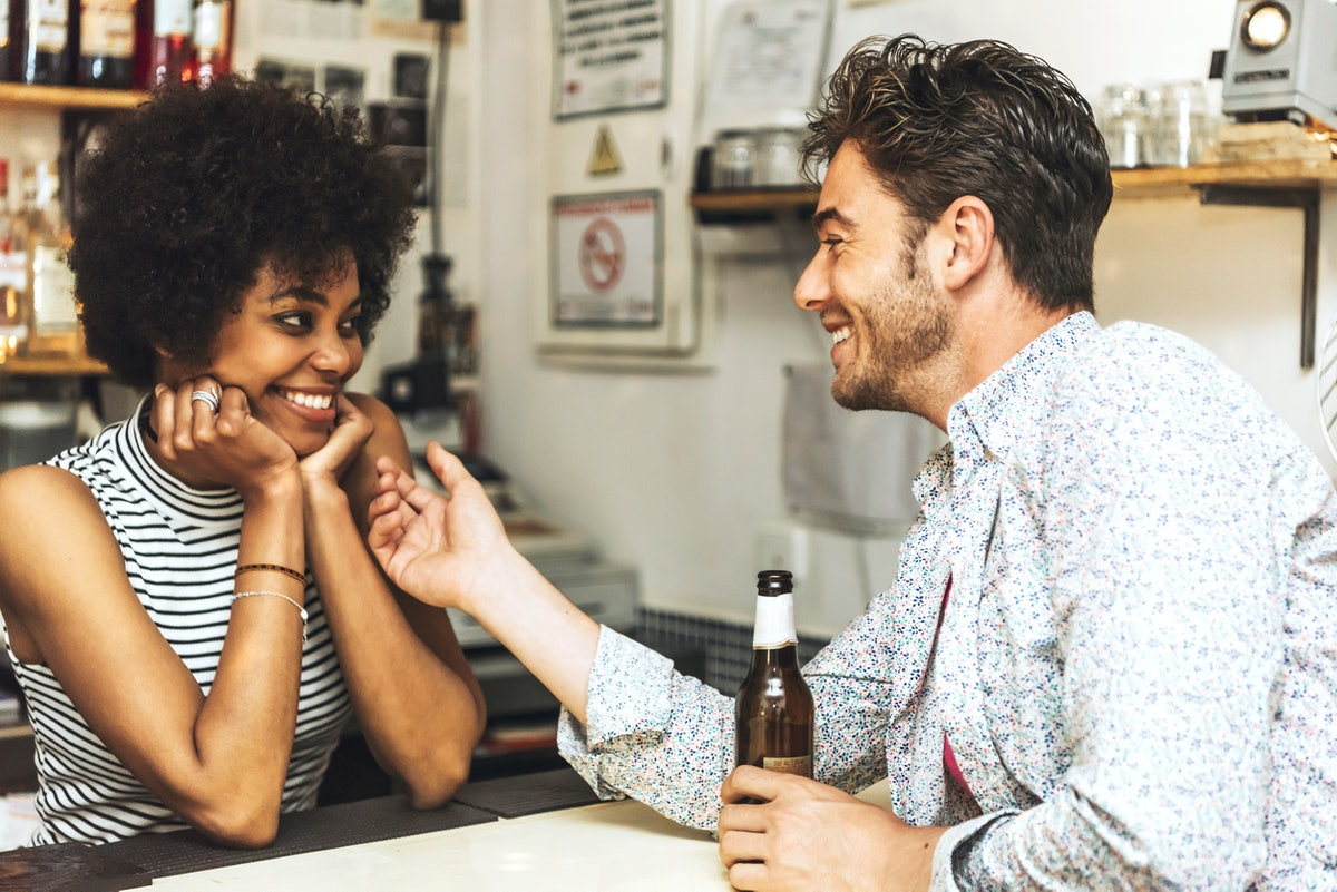 Young man holding bottle of beer and flirting with female bartender.