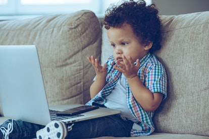 How does this thing turns on? Little African baby boy looking confused while sitting on the couch at home with laptop on his knees