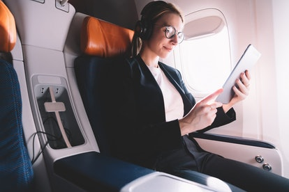 Caucasian woman traveler  using digital tablet while flying in first class cabin with access to internet connection on board, female passenger watching online movie via touch pad during flight