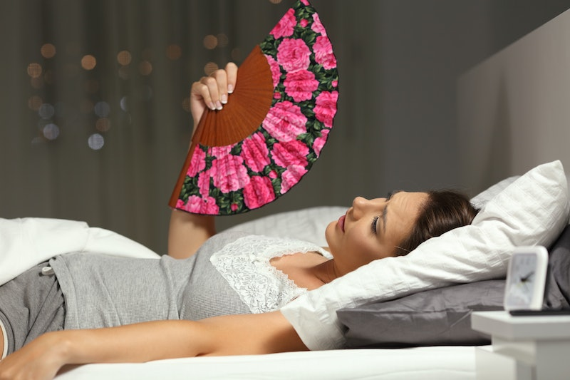 Overwhelmed woman fanning suffering heat stroke lying on the bed in the night at home