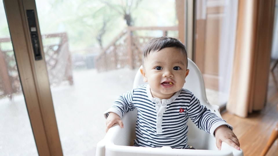 A cute baby boy on a baby high chair eating solid food and he is enjoying it.