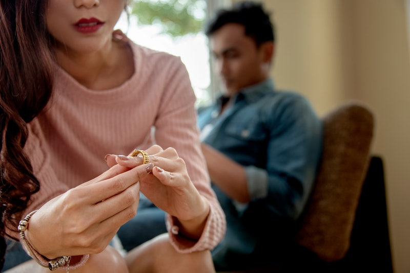 Close-up of a Sad Wife want to Divorce Lamenting Holding the Wedding Ring in a House Interior with B...