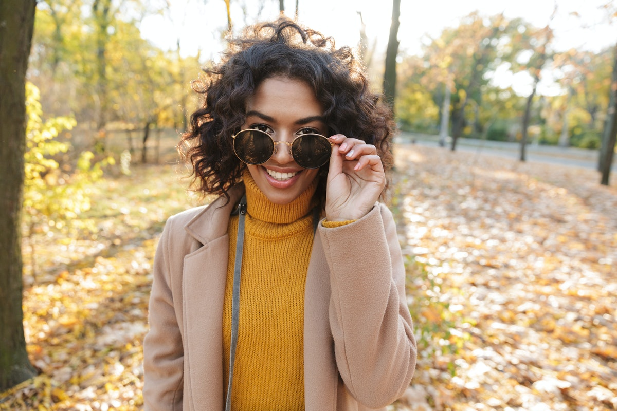 Smiling young african woman wearing autumn coat walking at the park