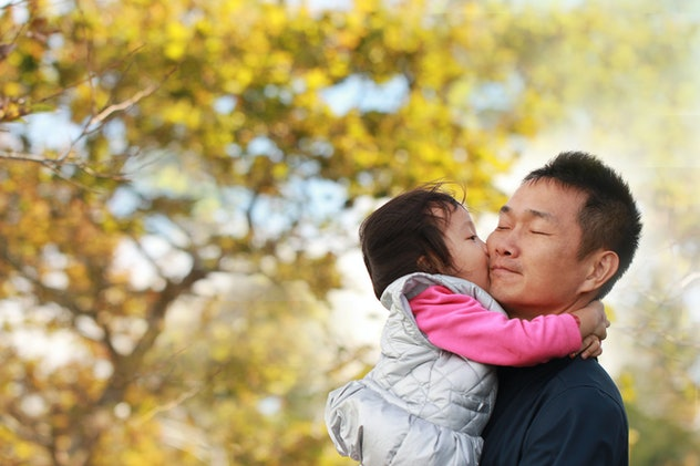 A Asian father holding and kissing baby girl before a golden tree on a meadow. Background for father's day