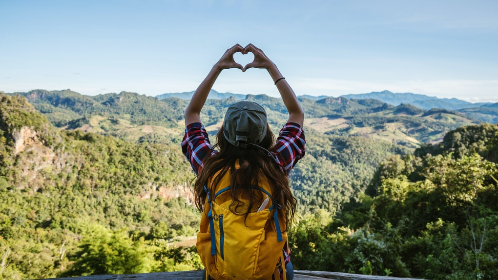 Young woman Tourists with backpacks Happy to travel She raised her hand to make a heart shape and enjoy the natural scenery on the mountain.