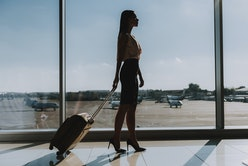 Stylish woman is standing near airport window. She is carrying suitcase and walking to plane