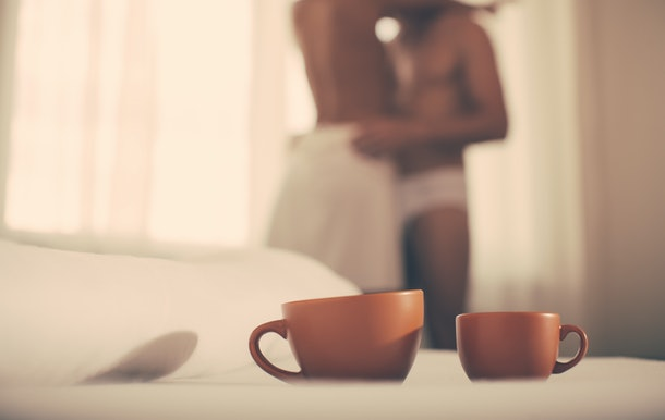 Luxury bedroom with cup of coffee. Two cups of coffee in morning. Passionate couple kissing, boy and girl. Having sex. Young lovers. People in love. Positions kamasutra. Erotic moments. Concept photo.