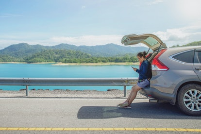 woman alone traveler on the road with sitting on hatchback car and playing smartphone with mountain and lake background , concept travel on holiday.