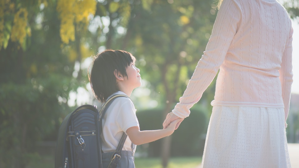 Asian mother holding hand of little son with backpack outdoors, back to school