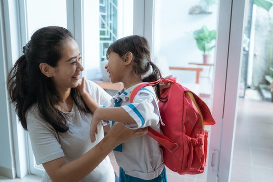 asian mother help her daughter to put the backpack on before going to school
