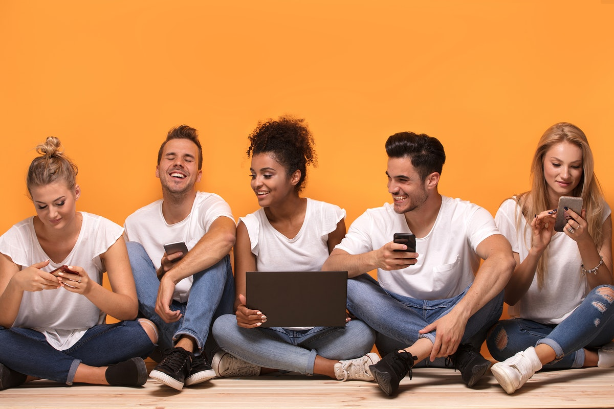 Group of young multiracial people looking at mobile phones, sitting on the floor, spending time together.