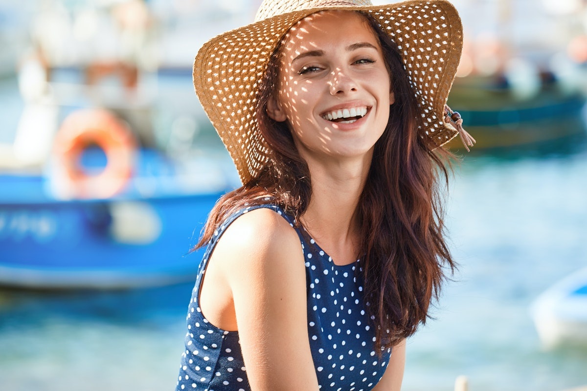 Portrait of a beautiful woman in a straw hat. Laughing girl. Summer time