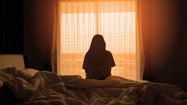 sadness woman sitting on the bed in the morning with sunlight from the windows