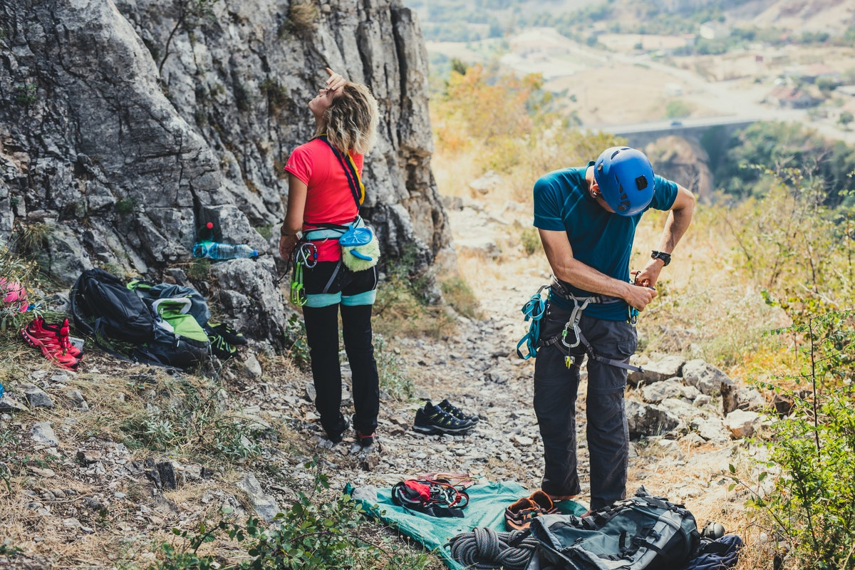 Male and female cimbers preparing equipment to climbe a rock.