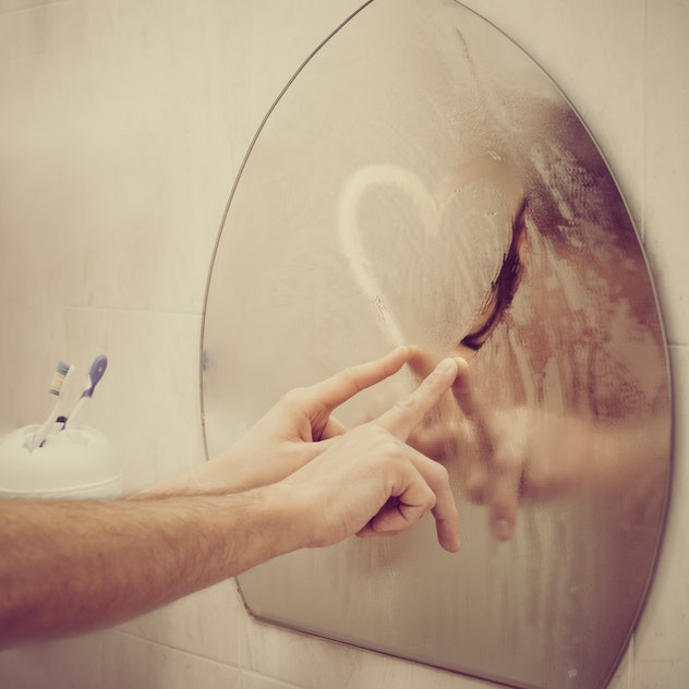 Couple in love drawing heart on misted mirror in bathroom, image with warm vintage toning