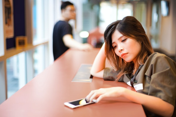 Lonely sad girl waiting for text message from smartphone on the table | Couple separated from each other