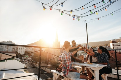 Outdoor shot of young people toasting drinks at a rooftop party. Young friends hanging out with drinks.