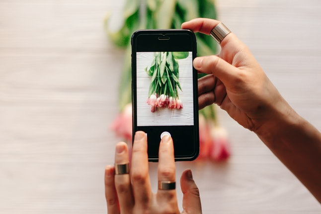 instagram photographer blogging workshop concept. hand holding phone and taking photo of stylish flowers. pink tulips on white wooden rustic background.space for text. hello spring