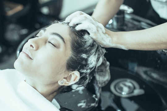 Hands of hairdresser washing hair of enjoying young Latin American woman with shampoo