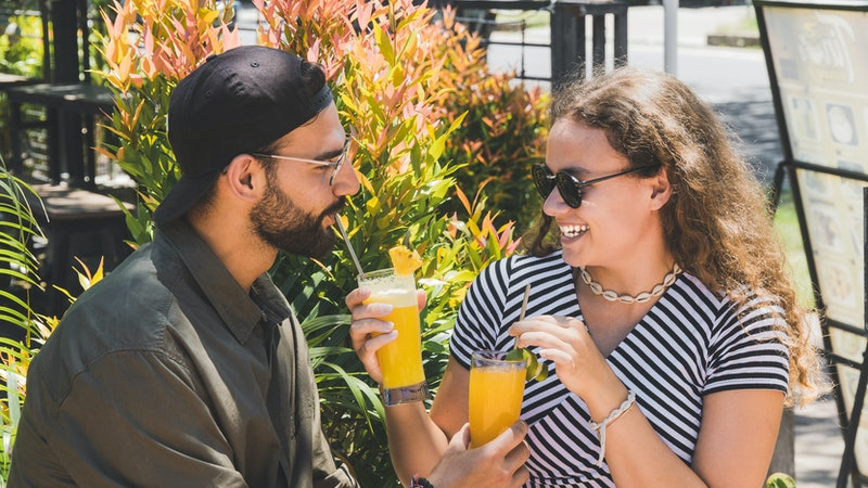 Beautiful woman giving her boyfriend drink while happily laughing – Young couple having fun on a date – Relationship lovers concept on a bright day – Image