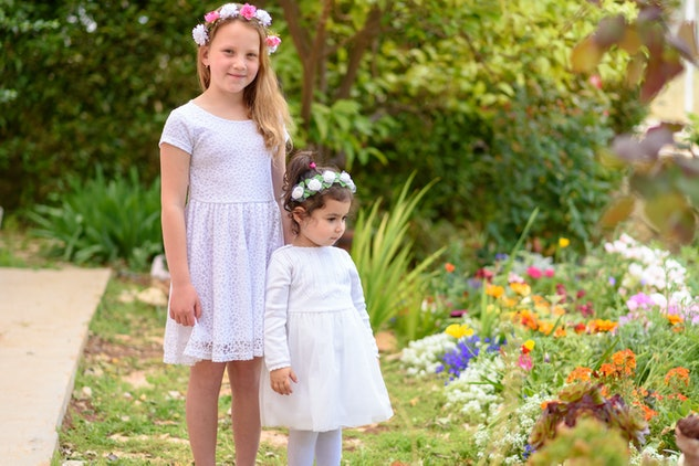 Two happy multiracial children with white dress and flower wreath playing outdoors. Kids having fun in summer or spring park. Beautiful girls on colorful nature background.