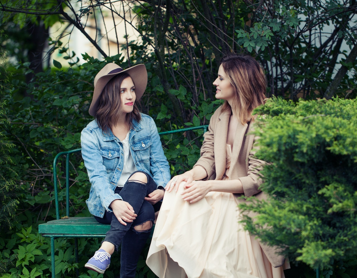 Pretty girls young friends chatting outdoors, lifestyle portrait