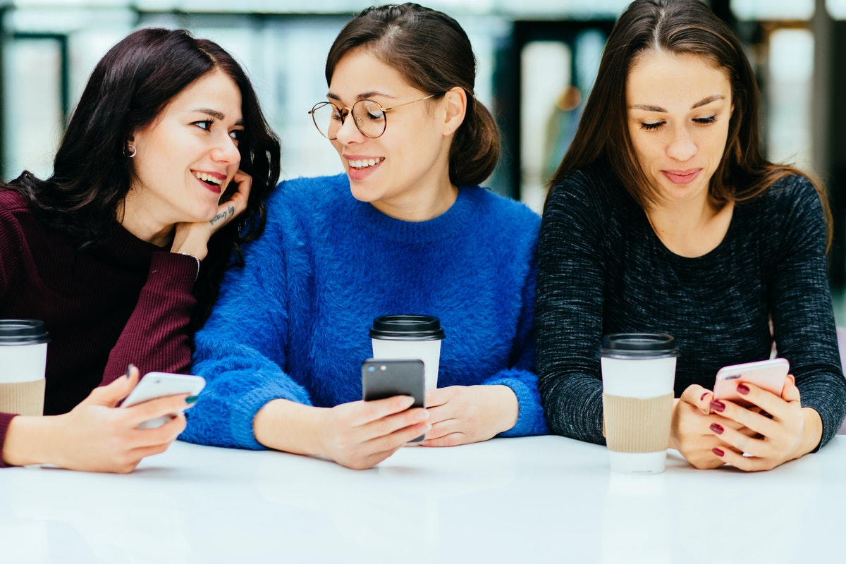 Group of three female students smiling, talking and looking in smart phone while drinking coffee from disposable cup in cafe.