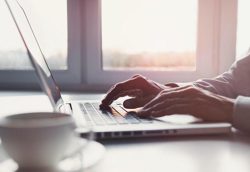 Business man using laptop computer. Male hand typing on laptop keyboard