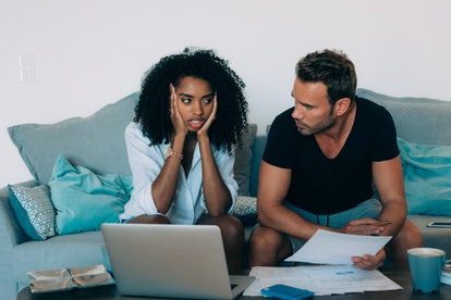 Young interracial couple in the couch stressed with financial problems doing calculations with paper work