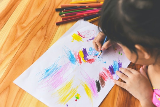 Girl painting on paper sheet with colour pencils on the wooden table at home / child kid doing drawi...