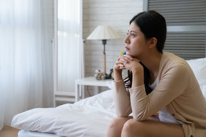 Unsmiling woman looking out window with curtain sitting in cozy bedroom in apartment. thoughtful depressed asian lady looks worried in bed. frustrated girl at home hands cross on chin frowning think