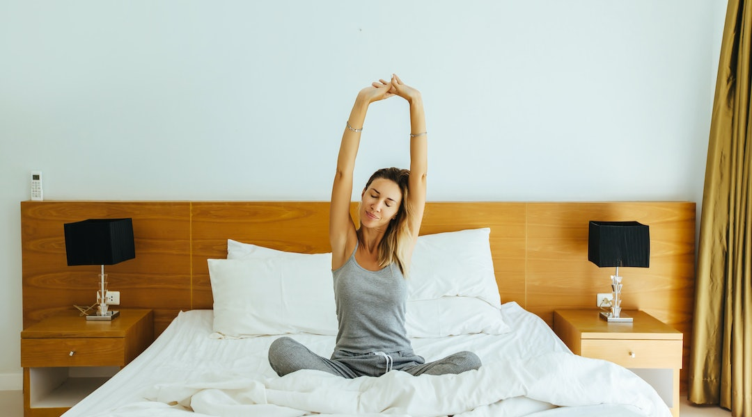 Woman waking up and stretching on bed in luxury hotel room in the morning. Sleeping well on comfy matress and pillows. Good starting of the day.