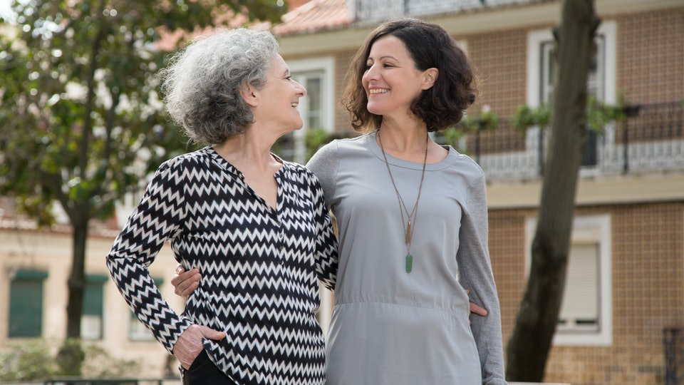 Cheerful smiling mother and daughter walking around uptown old district. Young and senior women hugging each other, chatting and laughing. Family relationship concept
