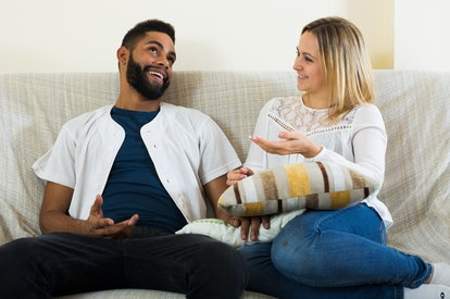 Young interracial couple talking in domestic interior