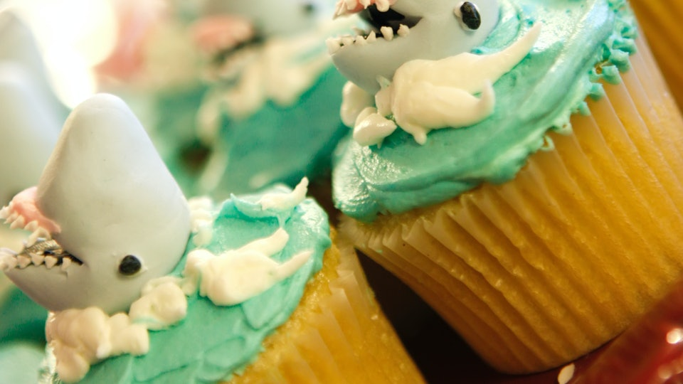 Unique cupcakes with sharks and green frosting with white.