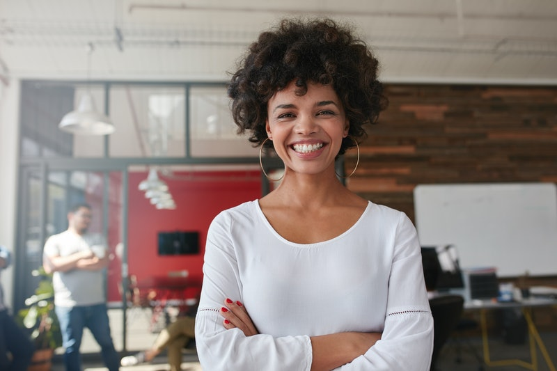 Smiling young woman standing with her arms crossed and looking at camera. She is standing in a modern office with her colleagues in the background.