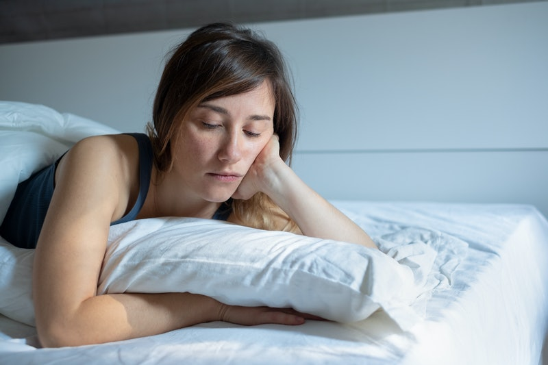 Sad woman can't sleep lying in her bed at home
