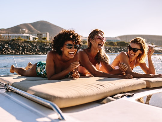 Three happy friends wearing swimsuits and sunglasses laugh while sunbathing on a yacht.