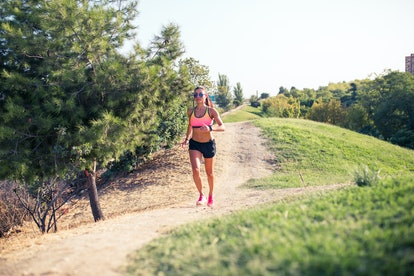 fit woman running outdoors in park on a sunny day