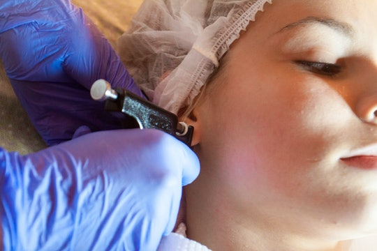 piercing ears to a girl in a spa salon by a doctor using a special device machine