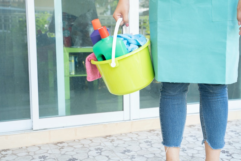 Women Cleaning with a bucket and cleaning products on blurred background. - Image