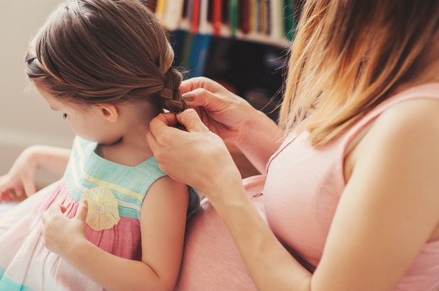 pregnant woman weaving braids with her toddler daughter at home