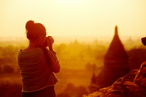 female traveler photographing temples at Bagan Myanmar Asia at sunrise