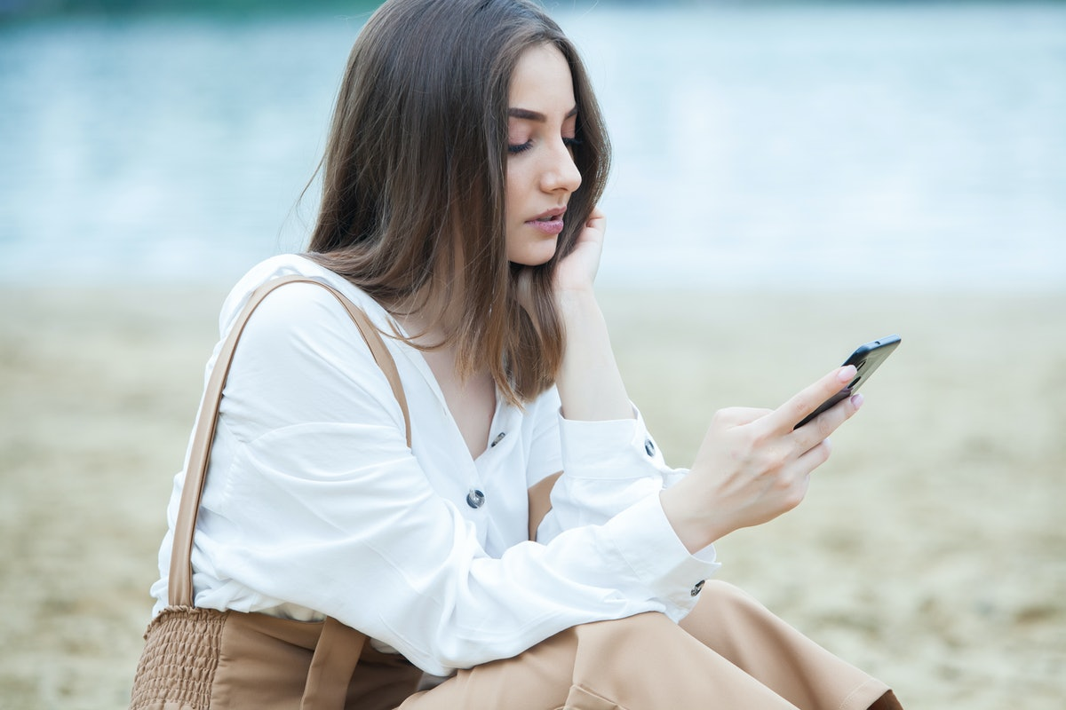 Girl outdoors texting on her mobile phone. Girl with phone. Portrait of a happy woman text sms message on her phone.