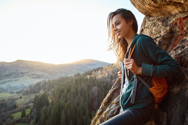 woman hiker with backpack, wearing in red jacket, sitting on edge of cliff against a forest and foggy valley background
