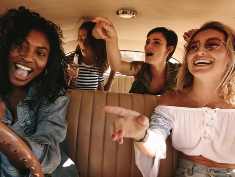 Young african woman driving the car with her friends having fun in the car. Crazy young female friends having lots of fun on road trip.