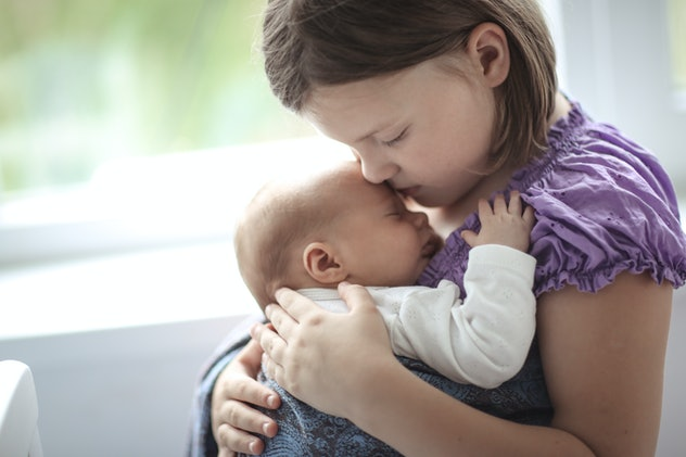 newborn baby in sling with rings , older sister takes care of the baby, large families and natural education and parenthood, bright interior