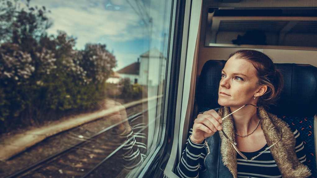 The young woman is on the train and watches through the window on the outside