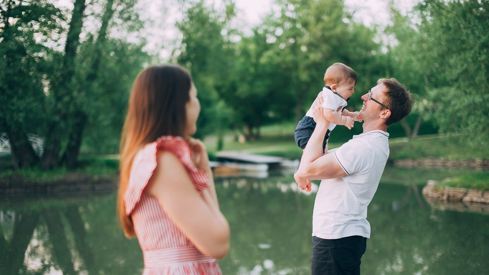family with a small child on the lake. mom and dad walk in nature with his son