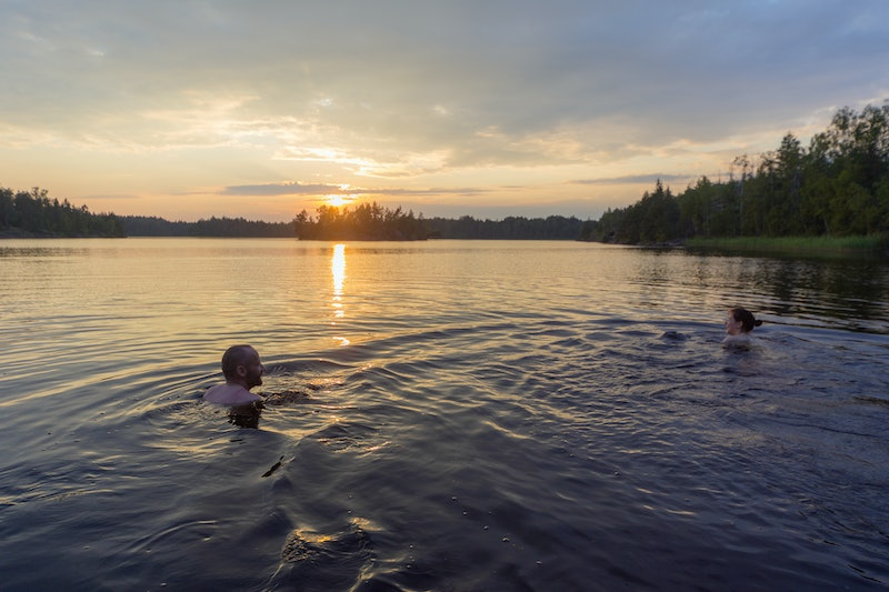 man and woman are swimming in the lake at sunset